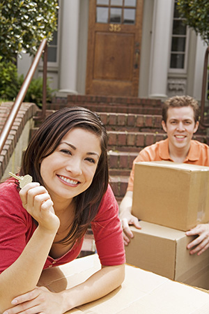 Buying a home: A man and woman with moving boxes and a house key.