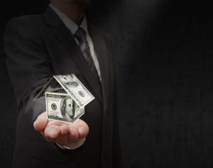 businessman shows dollars house